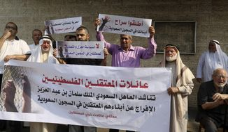 """Families of Palestinians held in jails in Saudi Arabia, hold placards in Arabic that some read, """"Release our sons in Saudi prisons, and No for the policy of isolation and torture for the prisoners in Saudi jails"""" during a protest, in front of the International Committee of the Red Cross office, in Gaza, Wednesday, Oct. 16, 2019. (AP Photo/Adel Hana)"""