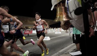 Yuki Kawauchi, of Japan, runs as the bell for the final lap is rung during the men's marathon at the World Athletics Championships in Doha, Qatar, Sunday, Oct. 6, 2019. (AP Photo/Nariman El-Mofty)