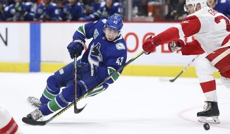 Vancouver Canucks' Quinn Hughes (43) is tripped by Detroit Red Wings' Mike Green (25) during the second period of an NHL hockey game Tuesday, Oct. 15, 2019, in Vancouver, British Columbia. (Ben Nelms/The Canadian Press via AP)