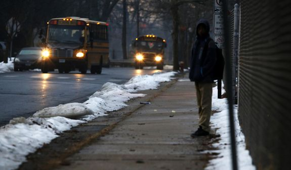In this Feb. 5, 2019, photo, a student waits for a bus outside the abandoned John C. Clark Elementary and Middle School in Hartford, Conn. The school was closed in 2015 after toxic PCBs were found during a renovation. Many students in the neighborhood now must travel long distances to get to other schools. (AP Photo/Martha Irvine)