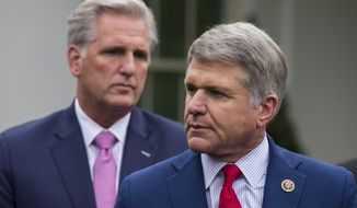 House Minority Leader Kevin McCarthy of Calif., left, stands as Rep. Michael McCaul, R-Texas, speaks with reporters after a meeting with President Donald Trump at the White House, Wednesday, Oct. 16, 2019, in Washington. (AP Photo/Alex Brandon)