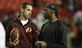 FILE - In this Dec. 15, 2013, file photo, then-Washington Redskins offensive coordinator Kyle Shanahan speaks to then-Washington Redskins quarterback Robert Griffin III, before the first half of an NFL football game against the Atlanta Falcons, in Atlanta. Kyle Shanahan is in a better place now. After serving as the Washington Redskins offensive coordinator under his dad, Mike Shanahan, from 2010-2013, he returns Sunday to face them as coach of the undefeated San Francisco 49ers. (AP Photo/John Bazemore, File)