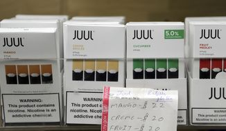 In this Thursday, Dec. 20, 2018 file photo, Juul products are displayed at a smoke shop in New York. On Thursday, Oct. 17, 2019, the company announced it will voluntarily stop selling its fruit and dessert-flavored vaping pods. (AP Photo/Seth Wenig) **FILE**