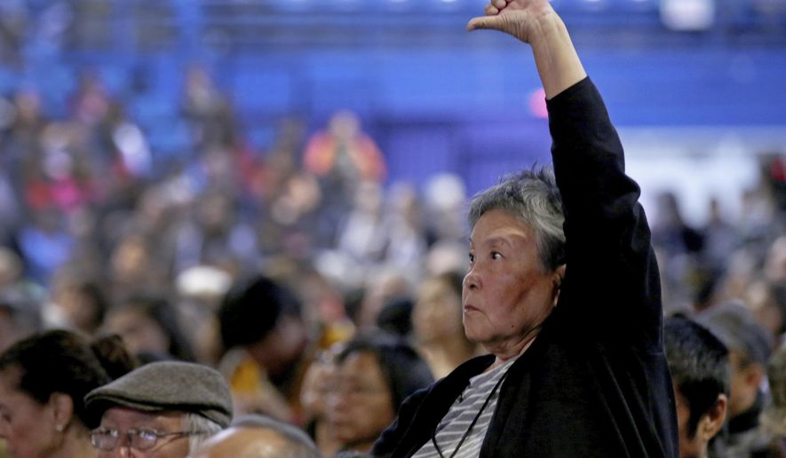 Dorothy Thomson stands while giving a thumbs down as Gov. Mike Dunleavy gives his State of Alaska Address during the 2019 Alaska Federation of Natives Convention Thursday, Oct. 17, 2019, in Fairbanks, Alaska. Republican Alaska Gov. Mike Dunleavy outlined plans aimed at improving public safety in rural Alaska during a speech Thursday to a major gathering of Alaska Natives that was interrupted by protests.(Eric Engman/Fairbanks Daily News-Miner via AP)