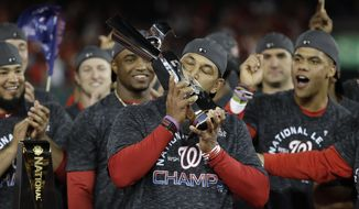 Washington Nationals manager Dave Martinez kisses the NLCS trophy after Game 4 of the baseball National League Championship Series against the St. Louis Cardinals Tuesday, Oct. 15, 2019, in Washington. The Nationals won 7-4 to win the series 4-0. (AP Photo/Jeff Roberson) **FILE**