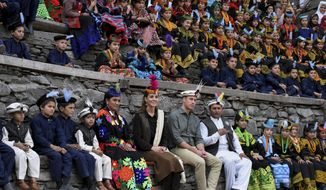 In this photo released by Press Information Department, Britain's Prince William, center, and his wife Kate sit with members of Kalash community and watching traditional dance during their visit to Bumburate Valley, an area of Pakistan's northern Chitral district, Wednesday Oct. 16, 2019. (Press Information Department via AP)