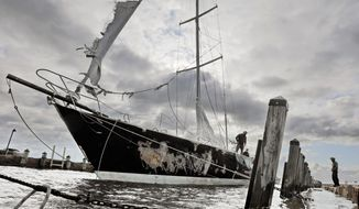 Concerned residents try to stabilize the 55-foot sailboat Fearless, which was damaged after it washed into a wharf in Mattapoisett harbor due to strong overnight winds, Thursday morning, Oct. 17, 2019, in Mattapoisett, Mass. ( Peter Pereira/Standard Times via AP)