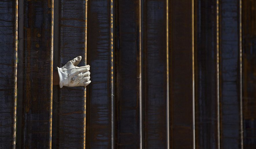 A construction worker's gloved hand is seen through a portion of the 30-foot tall bollard fence as work continues on the U.S./Mexico border fence two miles east of the Lukeville, Arizona port of entry on Oct. 8, 2019. An effort to overturn the president's direction of emergency funding for border-wall construction fell short of passage on Oct. 17 in the Senate. Photo taken from Sonoyta, Sonora, Mexico. (Mamta Popat/Arizona Daily Star via AP) **FILE**