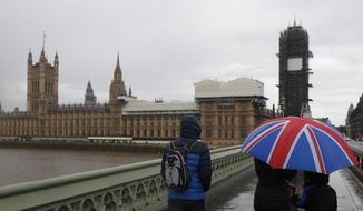 Tourists sheltering underneath a British Union flag umbrella walk across Westminster Bridge in the rain towards the Houses of Parliament in London, Thursday, Oct. 17, 2019. (AP Photo/Alastair Grant)