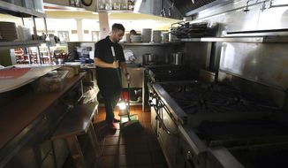 """FILE - In this Oct. 10, 2019, file photo, Salvador Espinosa sweeps in the kitchen of a Mary's Pizza Shack restaurant during a Pacific Gas and Electric Co. power shutdown in Santa Rosa, Calif. The California Senate will investigate a California utility's process for cutting off power to more than 2 million people to prevent wildfires. In a memo to the Senate Democratic Caucus on Thursday, Oct. 17, 2019, Senate President Pro Tempore Toni Atkins asked the Senate Energy, Utilities, and Communications Committee to """"begin investigating and reviewing options to address the serious deficiencies"""" with PG&E's current process of shutting off power to prevent wildfires. (Christopher Chung/The Press Democrat via AP, File)"""