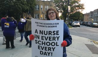 Third grade teacher Gay Niemeier pickets outside Sawyer Elementary School in Chicago, Thursday, Oct. 17, 2019, on the first day of a teacher's strike. Chicago teachers went on strike Thursday after failing to reach a contract deal with the nation's third-largest school district. (Rick Majewski/Chicago Sun-Times via AP)