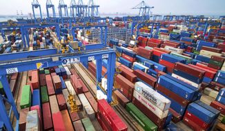 In this May 14, 2019, file photo, containers are piled up at a port in Qingdao in east China's Shandong province. (Chinatopix via AP, File)