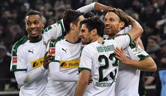 File---Picture taken Nov.25, 2018 shows Moenchengladbach's Michael Lang, right, is celebrated after scoring his side's second goal during the German Bundesliga soccer match between Borussia Moenchengladbach and Hannover 96 at the Borussia Park in Moenchengladbach, Germany, (AP Photo/Martin Meissner)