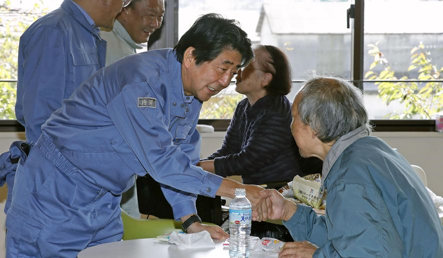 Japan's Prime Minister Shinzo Abe, front left, visits a shelter for people affected by Typhoon Hagibis, in Motomiya, Fukushima prefecture, Japan Thursday, Oct. 17, 2019. The typhoon hit Japan on Saturday with historic rainfall that caused rivers to overflow and left thousands of homes flooded, damaged or without power. (Shohei Miyano/Kyodo News via AP)