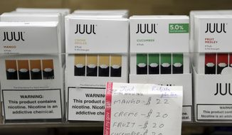 FILE - In this Thursday, Dec. 20, 2018 file photo, Juul products are displayed at a smoke shop in New York. On Thursday, Oct. 17, 2019, the company announced it will voluntarily stop selling its fruit and dessert-flavored vaping pods. (AP Photo/Seth Wenig)