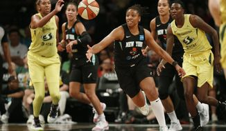 FILE - In this Aug. 11, 2019, file photo, New York Liberty guard Tanisha Wright, center, goes after a loose ball during the first half of the team's WNBA basketball game against the Seattle Storm at Barclays Center in New York. The Liberty will have a new home next year, playing their games at Barclays Center. Liberty team executives told the AP on Thursday that the franchise will play all its home contests at the Brooklyn arena that houses the Nets. The building was recently purchased by Liberty owner Joe Tsai, who also owns the Nets. Playing in Barclays Center is a huge upgrade for the Liberty, who played the past two seasons at the Westchester County Center, where the capacity was set for just over 2,000 fans. (AP Photo/Kathy Willens, File)