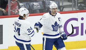 Toronto Maple Leafs center John Tavares, right, celebrates his goal with right wing Kasperi Kapanen (24), of Finland, during the third period of the team's NHL hockey game against the Washington Capitals, Wednesday, Oct. 16, 2019, in Washington. The Capitals won 4-3. (AP Photo/Nick Wass)