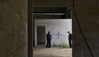 FILE - In this July 3, 2014 file photo, state police stand inside a warehouse where a black cross marks a wall near blood stains on the ground, after a shootout between Mexican soldiers and alleged criminals in Tlatlaya, Mexico. In a ruling made public on Thursday, Oct. 17, 2019, a court in Mexico has ordered the re-arrest of seven soldiers charged with abuse of authority for the 2014 army massacre. (AP Photo/Rebecca Blackwell, File)