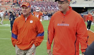 FILE - In this Sept. 17, 2011, file photo, then-offensive coordinators Chad Morris, left, of Clemson, and Gus Malzahn, right, of Auburn, walk together on the field at Memorial Stadium before an NCAA college football game, in Clemson, S.C. Morris is now the head coach at Arkansas. Malzahn is the head coach at Auburn. The two chat each week _ except when they play each other. (Mark Crammer/The Independent-Mail via AP, File)