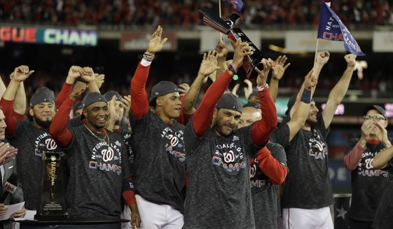 Washington Nationals manager Dave Martinez raises the NLCS trophy after Game 4 of the baseball National League Championship Series against the St. Louis Cardinals Tuesday, Oct. 15, 2019, in Washington. The Nationals won 7-4 to win the series 4-0. (AP Photo/Jeff Roberson)