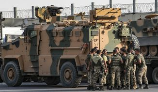 In this file photo, Turkish soldiers prepare to enter Syria aboard an armoured personnel carrier at the border with Syria in Karkamis, Gaziantep province, southeastern Turkey, Tuesday, Oct. 15, 2019. Turkey defied growing condemnation from its NATO allies to press ahead with its invasion of northern Syria on Tuesday, shelling suspected Kurdish positions near the border amid reports that Syrian Kurds had retaken a key town. (AP Photo/Emrah Gurel) **FILE**