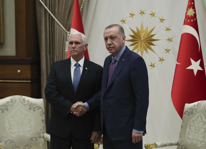 Turkey's President Recep Tayyip Erdogan, right, shakes hands with U.S Vice President Mike Pence, prior to their talks at the Presidential Palace in Ankara, Turkey, Thursday, Oct. 17, 2019. A high level U.S. delegation arrived in Turkey on Thursday for talks on a cease-fire in Syria. (Presidential Press Service via AP, Pool)