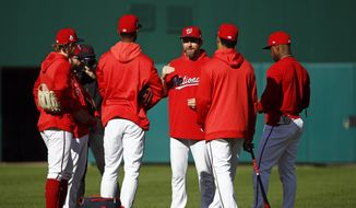 Washington Nationals third base coach Bob Henley, center, speaks with players during a baseball workout, Friday, Oct. 18, 2019, in Washington, in advance of the team's appearance in the World Series. (AP Photo/Patrick Semansky) **FILE**