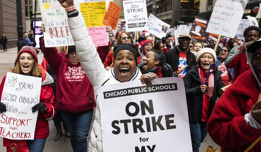 Thousands of striking Chicago Teachers Union members and their supporters march through the Loop, Thursday, Oct. 17, 2019, in Chicago.Striking teachers went on strike after their union and city officials failed to reach a contract deal in the nation's third-largest school district. (Ashlee Rezin Garcia/Chicago Sun-Times via AP)