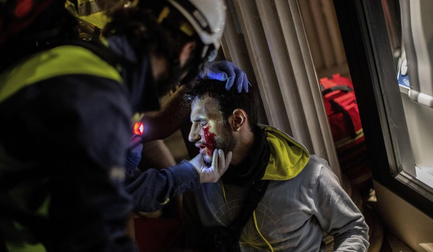 Paramedics attend a protestor during clashes with police in Barcelona, Spain, early Friday, Oct. 18, 2019. Catalonia's separatist leader vowed Thursday to hold a new vote to secede from Spain in less than two years as the embattled northeastern region grapples with a wave of violence that has tarnished a movement proud of its peaceful activism. (AP Photo/Bernat Armangue)