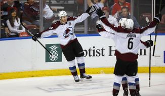 Colorado Avalanche center Nathan MacKinnon (29) celebrates with teammates after he scored in overtime of the team's NHL hockey game against the Florida Panthers, Friday, Oct. 18, 2019 in Sunrise, Fla. The Avalanche won 5-4. (AP Photo/Wilfredo Lee)