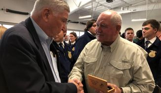 U.S. Secretary of Agriculture Sonny Perdue, right, shakes hands with a member of the agriculture industry who attended a town hall meeting on Friday, Oct. 18, 2019, in Memphis, Tenn. (AP Photo/Adrian Sainz)