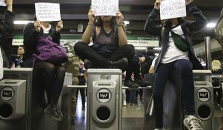 "Holding signs that read in Spanish, from left, ""We pay Cops Salaries and subway fare, and here they are against us,"" ""Save on your ticket"" and ""The people united will never be defeated,"" students block the turnstiles to the subway protesting against the rising cost of subway and bus fare, in Santiago, Friday, Oct. 18, 2019. (AP Photo/Esteban Felix)"