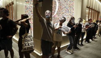 Protesters takes selfies while wearing masks during a protest in Hong Kong, Friday, Oct. 18, 2019. Hong Kong pro-democracy protesters are donning cartoon/superhero masks as they formed a human chain across the semiautonomous Chinese city, in defiance of a government ban on face coverings. (AP Photo/Mark Schiefelbein)