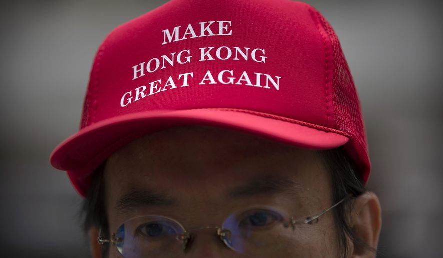 "A demonstrator wears a hat reading ""Make Hong Kong great again"" during a rally in the Central District in Hong Kong, Friday, Oct. 18, 2019. Hundreds of demonstrators marched through the heart of Hong Kong on Friday afternoon in a ""flash mob"" gathering as part of continuing pro-democracy protests on the city. (AP Photo/Mark Schiefelbein)"
