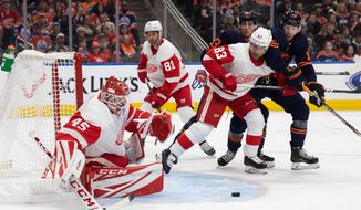 Detroit Red Wings goaltender Jonathan Bernier (45) watches the puck as teammate Trevor Daley (83) defends against Edmonton Oilers center Ryan Nugent-Hopkins (93) and left wing James Neal (18) during the second period of an NHL hockey game Friday, Oct. 18, 2019, in Edmonton, Alberta. (Codie McLachlan/The Canadian Press via AP)