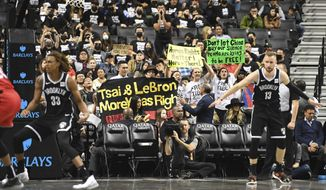 People raise signs referencing Tibet and Hong Kong during the fourth quarter of a preseason NBA basketball game between the Toronto Raptors and the Brooklyn Nets, Friday, Oct. 18, 2019, in New York. (AP Photo/Sarah Stier)