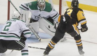 Brandon Tanev (13) shoots on Dallas Stars goaltender Anton Khudobin during the first period of an NHL hockey game Friday, Oct. 18, 2019, in Pittsburgh. (AP Photo/Keith Srakocic)