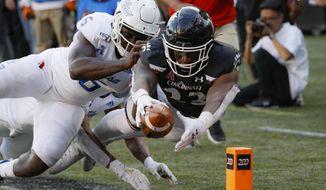 Cincinnati running back Gerrid Doaks (23) scores a touchdown against Tulsa linebacker Diamon Cannon (6) during the second half of an NCAA college football game, Saturday, Oct. 19, 2019, in Cincinnati. (AP Photo/John Minchillo)