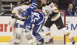 Toronto Maple Leafs' Auston Matthews (34) gets checked by Boston Bruins' Brandon Carlo (25) in front of the Bruins' net during first period NHL hockey action in Toronto, Saturday, Oct. 19, 2019. (Fred Thornhill/The Canadian Press via AP)