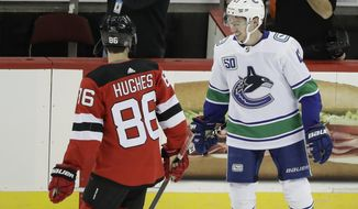 Vancouver Canucks' Quinn Hughes, right, talks to his brother New Jersey Devils' Jack Hughes, left, before of an NHL hockey game Saturday, Oct. 19, 2019, in Newark, N.J. The Devils won 1-0. (AP Photo/Frank Franklin II)