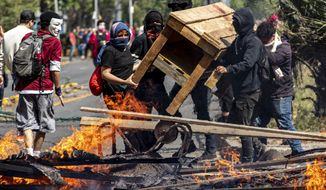 Demonstrators build a burning barricade during a protest in Santiago, Chile, Saturday, Oct. 19, 2019. The protests started on Friday afternoon when high school students flooded subway stations, jumping turnstiles, dodging fares and vandalizing stations as part of protests against a fare hike, but by nightfall had extended throughout Santiago with students setting up barricades and fires at the entrances to subway stations, forcing President Sebastian Pinera to announce a state of emergency and deploy the armed forces into the streets. (AP Photo/Esteban Felix)