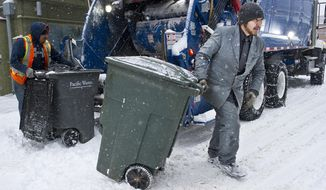 "FILE - In this Dec. 7, 2016, file photo, Charlie Gallant, right, empties garbage containers with Brian Felipe, left, for Pacific Waste on South Franklin Street in Juneau, Alaska. Gallant said, ""Last week I saw a man walking with a coat and tie talking on his phone and I told by buddy I wish I had a job where I could wear a coat and tie. So why not! I decided I would wear a coat and tie all week. When I look good I feel good."" Three years ago, Empire staff photographer Michael Penn took a photograph of a garbage collector emptying a trash can for the city of Juneau in a suit and tie. Gallant started a new job as a car salesperson in Anchorage last week. (Michael Penn/The Juneau Empire via AP, File)"