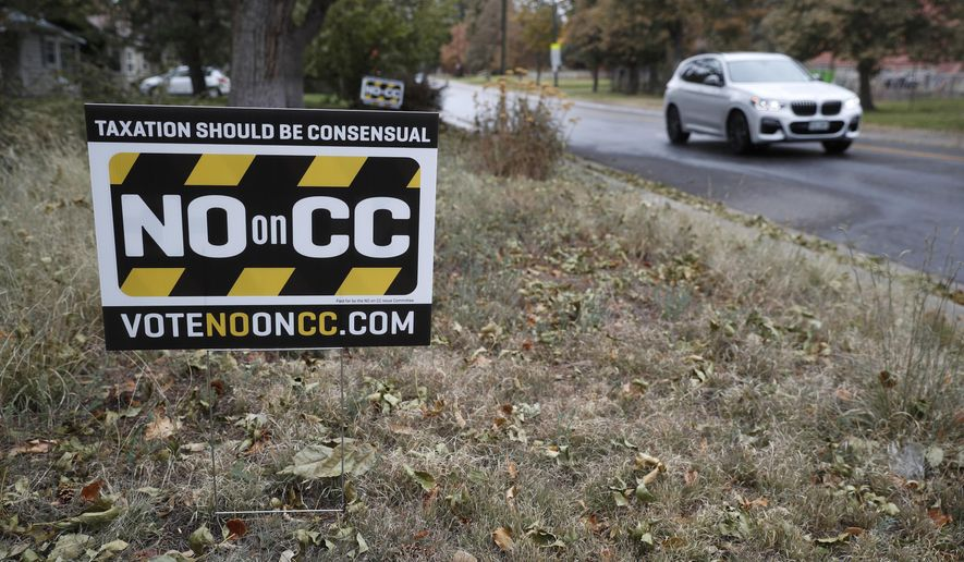A vehicle passes by a lawn sign calling for voters to cast ballots against a measure to dismantle part of Colorado's state tax laws on election day Tuesday, Nov. 5. (AP Photo/David Zalubowski)