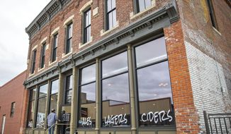 A man walks into Stone Hollow Brewing Company Wednesday, Oct 9, 2019, in Beatrice, Neb. Todd and Soni Hydo spearheaded the project of rehabilitating the 140-year-old-building. (Kayla Wolf/The World-Herald via AP)
