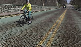 """FILE - In this Tuesday April 16, 2019 file photo Cheryl Dirth, Burlington, rides her bicycles across Cascade Bridge before City of Burlington Street Department workers install the fencing closing off the bridge to foot and bicycle traffic in Burlington, Iowa. The Burlington City Council decided to vote to close the bridge after reviewing the findings of the 2008 study of the bridge, which concluded that """"Cascade Bridge is in poor condition and as such is a safety hazard."""". (John Lovretta/The Hawk Eye via AP)"""