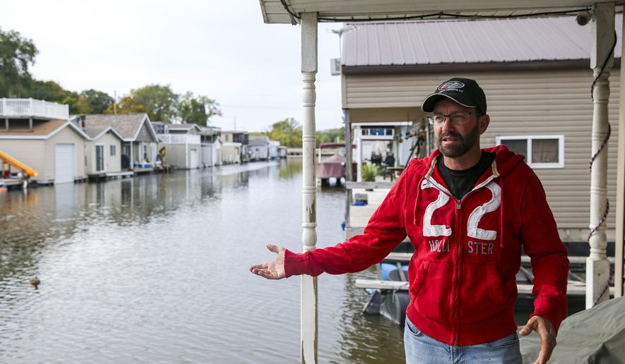 In this Wednesday, Oct. 9, 2019, photo, John Hansen, of Cedar Rapids, Iowa, an Ellis Harbor home owner of six years, talks about his experiences having a home on the harbor while standing on the back porch of neighbor, Deanna McLaud, in Cedar Rapids. Cedar Rapids struggles to maintain the rare houseboat harbor. (Andy Abeyta/The Gazette via AP)