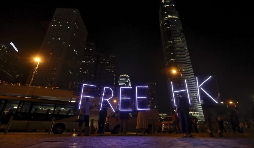 Protesters use illumination lights form a slogan as they attend a prayer rally at Edinburgh Place in Hong Kong, Saturday, Oct. 19, 2019. Hong Kong pro-democracy protesters are set for another weekend of civil disobedience as they prepare to hold an unauthorized protest march to press their demands. (AP Photo/Mark Schiefelbein)