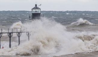 Large waves, on Lake Michigan, caused by high winds, crash into the Saint Joseph Lighthouse and pier on Wednesday, Oct. 16, 2019, in Saint Joseph, Mich. (Robert Franklin/South Bend Tribune via AP)