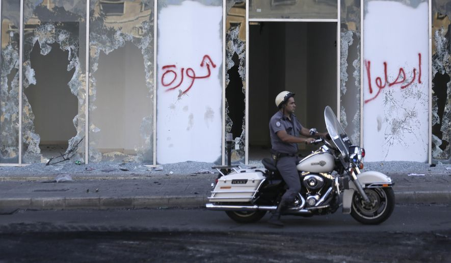"A motorcycle police officer passes by broken glass doors of a shop in the aftermath of a protest against the Lebanese government in Beirut, Lebanon, Saturday, Oct. 19, 2019. The blaze of protests was unleashed a day earlier when the government announced a slate of new proposed taxes, including a $6 monthly fee for using Whatsapp voice calls. Arabic on the wall reads ""Revolution, left, Leave."" (AP Photo/Hassan Ammar)"