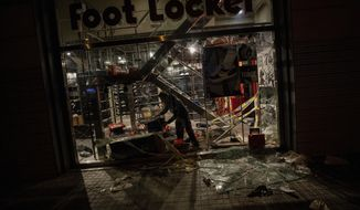 A worker inspects a vandalize shop in Barcelona, Spain, Saturday, Oct. 19, 2019. Masses of flag-waving demonstrators demanding Catalonia's independence and the release from prison of separatist leaders jammed downtown Barcelona on Friday as the northeastern Spanish region endured its fifth straight day of unrest. On Friday, the demonstrations were mostly peaceful, though police clashed with a few hundred young protesters who hurled bottles, eggs and paint at the gates of the police headquarters in the center of the city. Large trash containers were burned before police responded, using rubber bullets and tear gas to disperse the crowds. (AP Photo/Bernat Armangue)